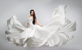 Красивая маленькая девочка в белом платье летая пропускать ткани Светлое белое летание ткани стоковые изображения