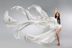Красивая маленькая девочка в белом платье летая пропускать ткани Светлое белое летание ткани стоковые фотографии rf