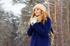 Красивая маленькая девочка в синем пиджаке и с сумкой на ее назад и выпивая чае Девушка перемещения Стоковое Фото