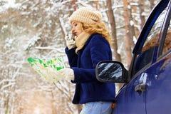 Красивая маленькая девочка в синем пиджаке стоя около автомобиля, держа карту в руке и выпивая чай Девушка перемещения Стоковые Изображения
