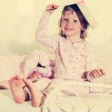 Красивая маленькая девочка в шпаргалке с книгой на вашей голове Стоковая Фотография