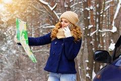 Красивая маленькая девочка говоря на телефоне и держа карту в ее руке, стоя близко автомобиль в девушке перемещения леса Стоковые Изображения RF