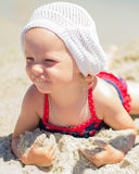 Красивая маленькая девочка лежа на пляже Стоковые Изображения