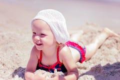 Красивая маленькая девочка лежа на пляже Стоковая Фотография RF