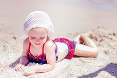 Красивая маленькая девочка лежа на пляже Стоковое фото RF