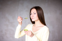 Красивая маленькая девочка держа киви еда здоровая Стоковое Изображение