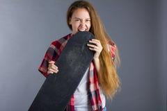 Красивая маленькая девочка жует на скейтборде Стоковое фото RF