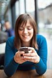 Красивая маленькая девочка используя умный телефон в кафе Стоковые Фотографии RF