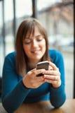 Красивая маленькая девочка используя умный телефон в кафе Стоковое Изображение RF