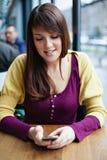Красивая маленькая девочка используя умный телефон в кафе Стоковое фото RF