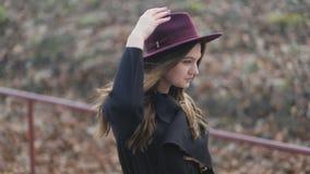 Красивая маленькая девочка идет вниз в парк, длинные волосы, пальто осени, держа ее шляпу, взгляд со стороны, медленная съемка st сток-видео