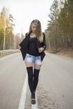 Красивая маленькая девочка идя вниз с дороги в лесе Стоковые Фотографии RF