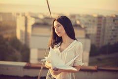 Красивая маленькая девочка на крыше с краном бумаги origami стоковая фотография rf