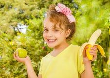 Красивая маленькая девочка, нося желтую футболку держа здоровые яблоко и банан, в предпосылке сада стоковые фото