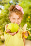 Красивая маленькая девочка нося желтую футболку держа здоровый банан и указывая внутри от ее яблоко, в a стоковые фото