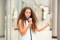 Красивая маленькая девочка оплачивая кредитной карточкой для Стоковое Изображение