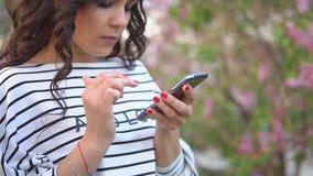 Красивая маленькая девочка посылает сообщение к мобильному телефону к вашим друзьям движение медленное сток-видео