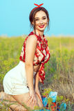 Красивая маленькая девочка при совершенная улыбка уговаривать нося красную блузку, белые шорты и держатель сидя в поле стоковое фото rf