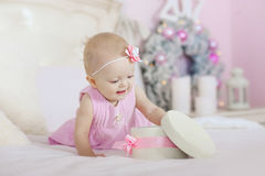 Красивая маленькая девочка раскрывая подарок рождества, дерево предпосылки стоковое фото rf