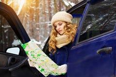 Красивая маленькая девочка сидит в автомобиле и карта держать в ее руках, нося синий пиджак Девушка перемещения Стоковое фото RF