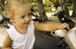 Красивая маленькая девочка сидя на велосипеде в парке она рассматривает и изучает ее Стоковые Фотографии RF