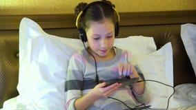 Красивая маленькая девочка сидя на кровати в гостинице в наушниках и играя игру на smartphone акции видеоматериалы