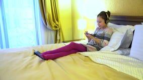 Красивая маленькая девочка сидя на кровати в гостинице в наушниках и играя игру на smartphone видеоматериал