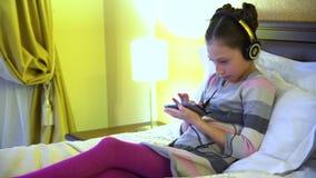 Красивая маленькая девочка сидя на кровати в гостинице в наушниках и играя игру на smartphone сток-видео