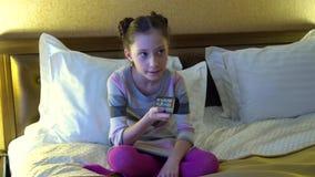 Красивая маленькая девочка сидя на кровати в гостинице и смотря ТВ В руках девушки держа дистанционное управление акции видеоматериалы