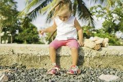 Красивая маленькая девочка сидя на портовом районе и играх Стоковое Изображение RF