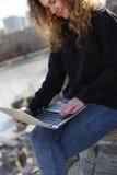 Красивая маленькая девочка сидя с компьтер-книжкой в парке Возможности бесконечны на интернете Стоковое фото RF