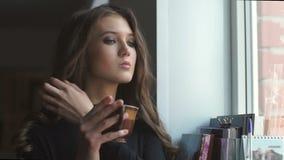 Красивая маленькая девочка смотрит через окно и выпивает coffe сток-видео