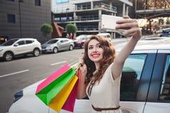 Красивая маленькая девочка стоит около белого автомобиля, делает покупки, selfie Стоковое Фото