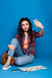 Красивая маленькая девочка с красными губами на голубой предпосылке делая selfie Стоковое Изображение