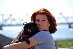 Красивая маленькая девочка с красными объятиями волос на улице любимчика черная собака породы мопс Стоковое Фото