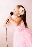Красивая маленькая девочка с микрофоном в платье принцессы Стоковые Изображения RF