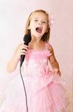 Красивая маленькая девочка с микрофоном в платье принцессы Стоковое Фото