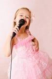 Красивая маленькая девочка с микрофоном в платье принцессы Стоковая Фотография