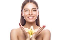 Красивая маленькая девочка с светлым естественным составом и совершенная кожа с цветками в ее руке Сторона красотки Стоковая Фотография