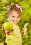 Красивая маленькая девочка, wearinmg желтая футболка держа здоровые яблоко и банан, в предпосылке сада стоковое фото rf