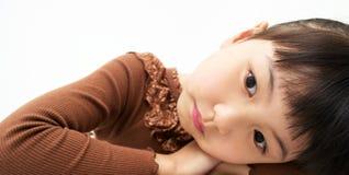 Красивая маленькая маленькая девочка отдыхает ее подбородок на ее руках стоковые изображения rf