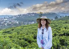 Красивая милая женщина в шляпе усмехаясь пока стоящ на плантации чая стоковые изображения rf