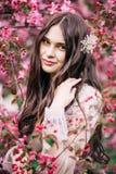 Красивая милая невеста девушки в платье шнурка будуара прозрачном, с украшением на волосах, усмехаться, смотря вокруг цветения де Стоковое Изображение
