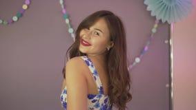 Красивая милая привлекательная счастливая молодая женщина брюнет представляя в волосах флористического платья касающих усмехаясь  акции видеоматериалы