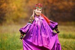 Красивая милая девушка в национальном ярком фиолетовом платье с красной банданой на ее голове, орнаментах и вышивке цветасто Стоковая Фотография