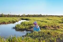 Красивая милая маленькая девочка в голубом платье сидя заводью Стоковое Фото