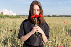 Красивая милая сексуальная молодая женщина с полными губами с короткими волосами в поле с маком цветет в их руках Стоковые Изображения RF