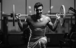 Красивая модельная разминка молодого человека в спортзале Стоковое Изображение RF