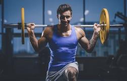 Красивая модельная разминка молодого человека в спортзале Стоковое фото RF
