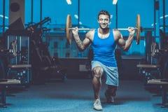 Красивая модельная разминка молодого человека в спортзале Стоковая Фотография RF